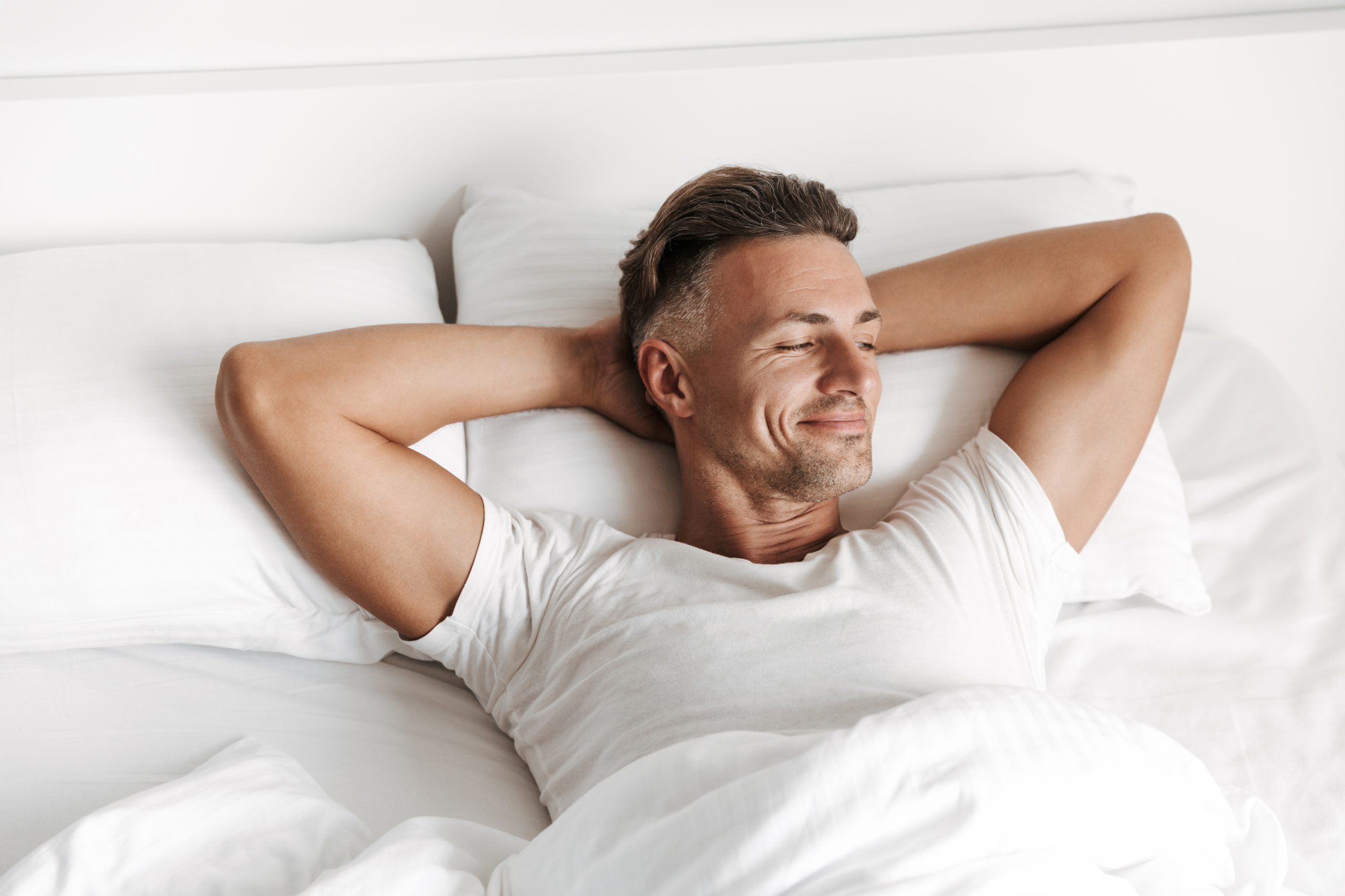 Satisfied man relaxing in bed