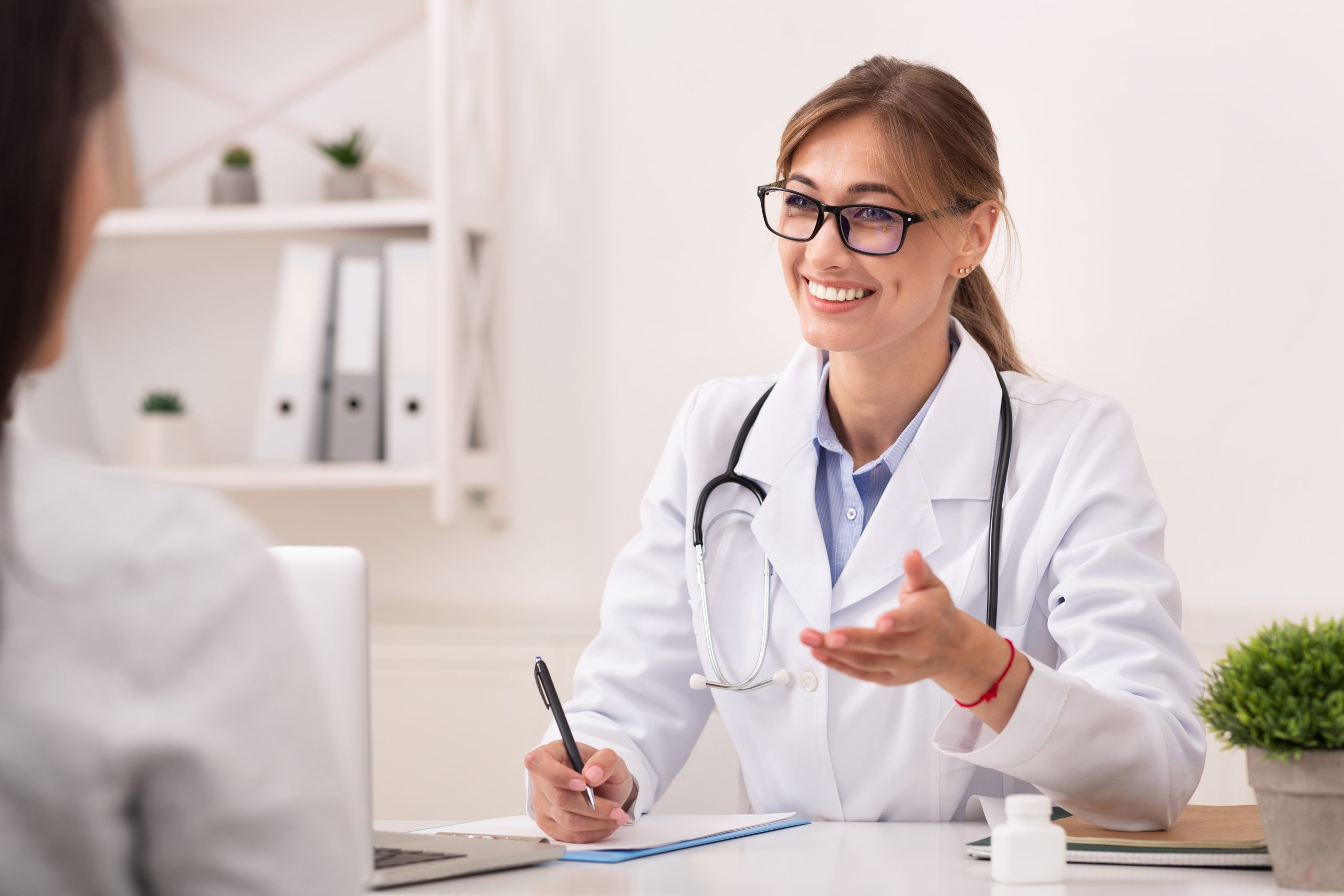 Smiling Doctor Woman Talking With Unrecognizable Patient Sitting In Office