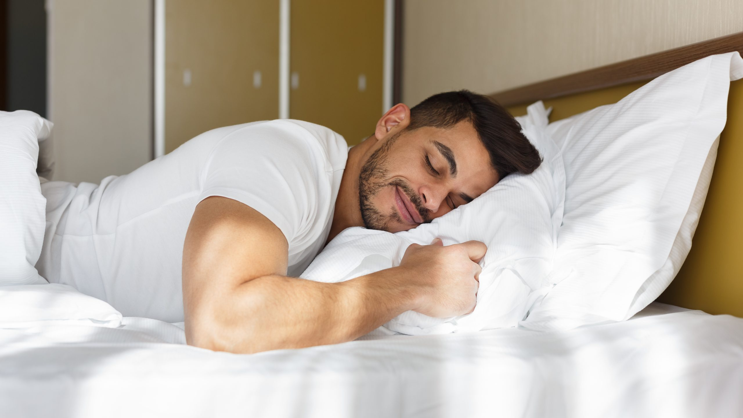 Young man peacefully sleeping in his bed - International