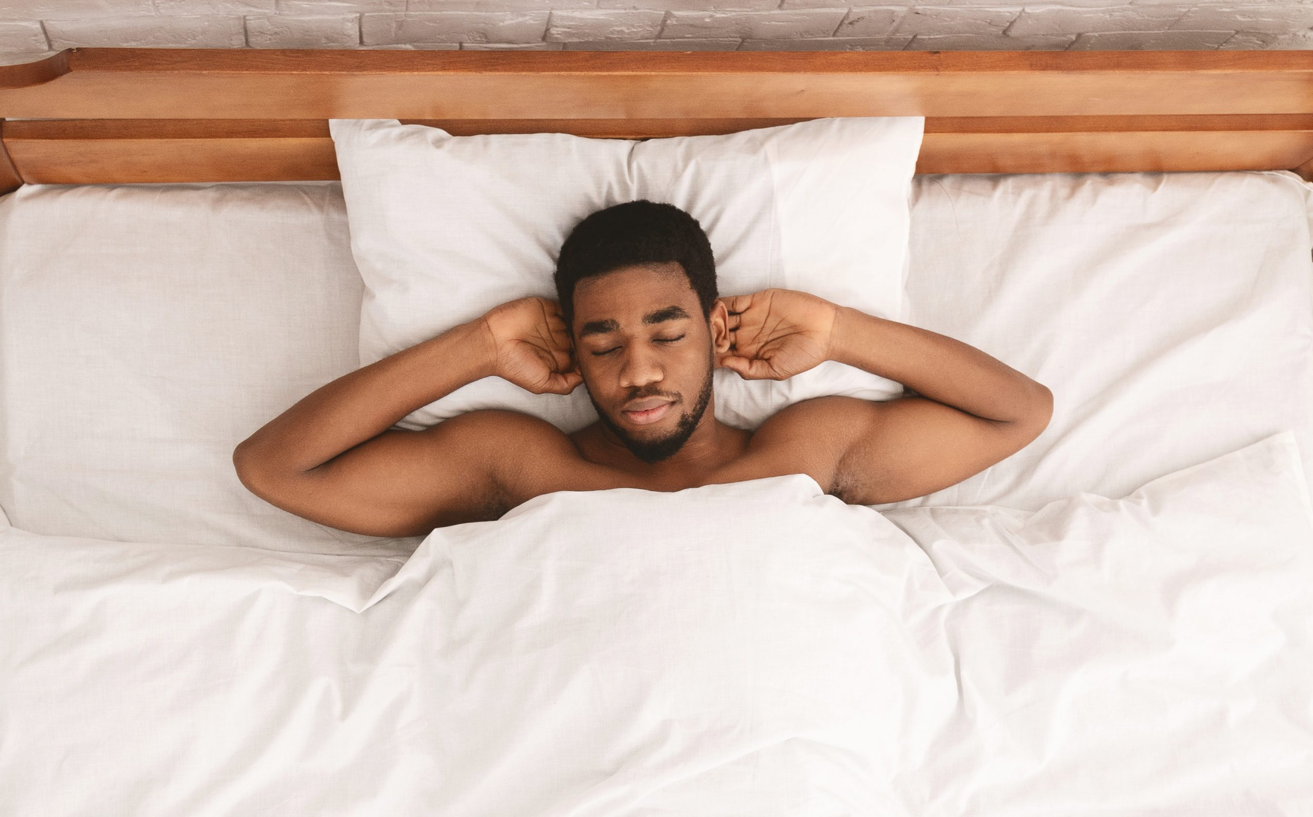 Relaxed black guy lying with hands behind head