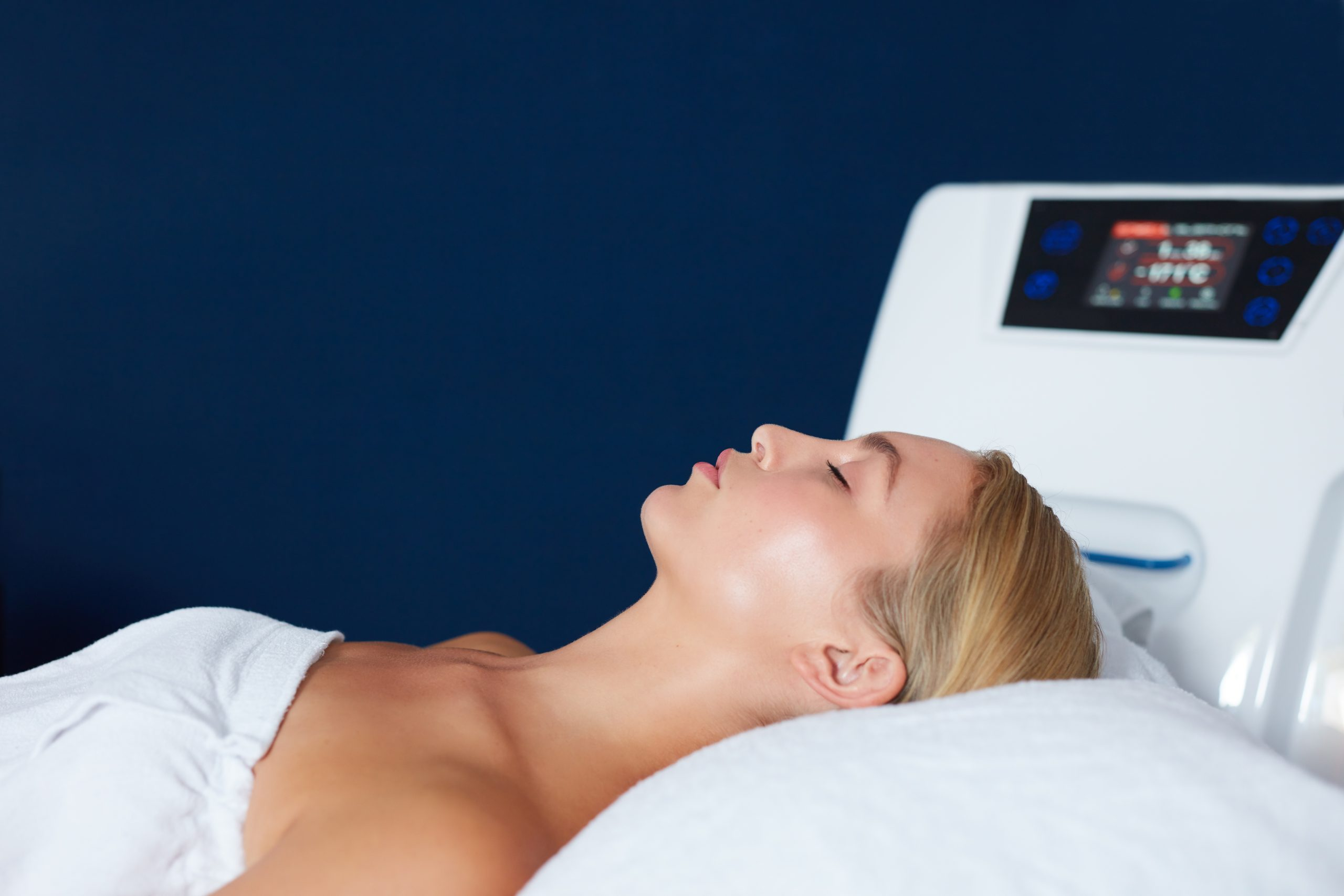 Young woman lying on massage table at spa clinic