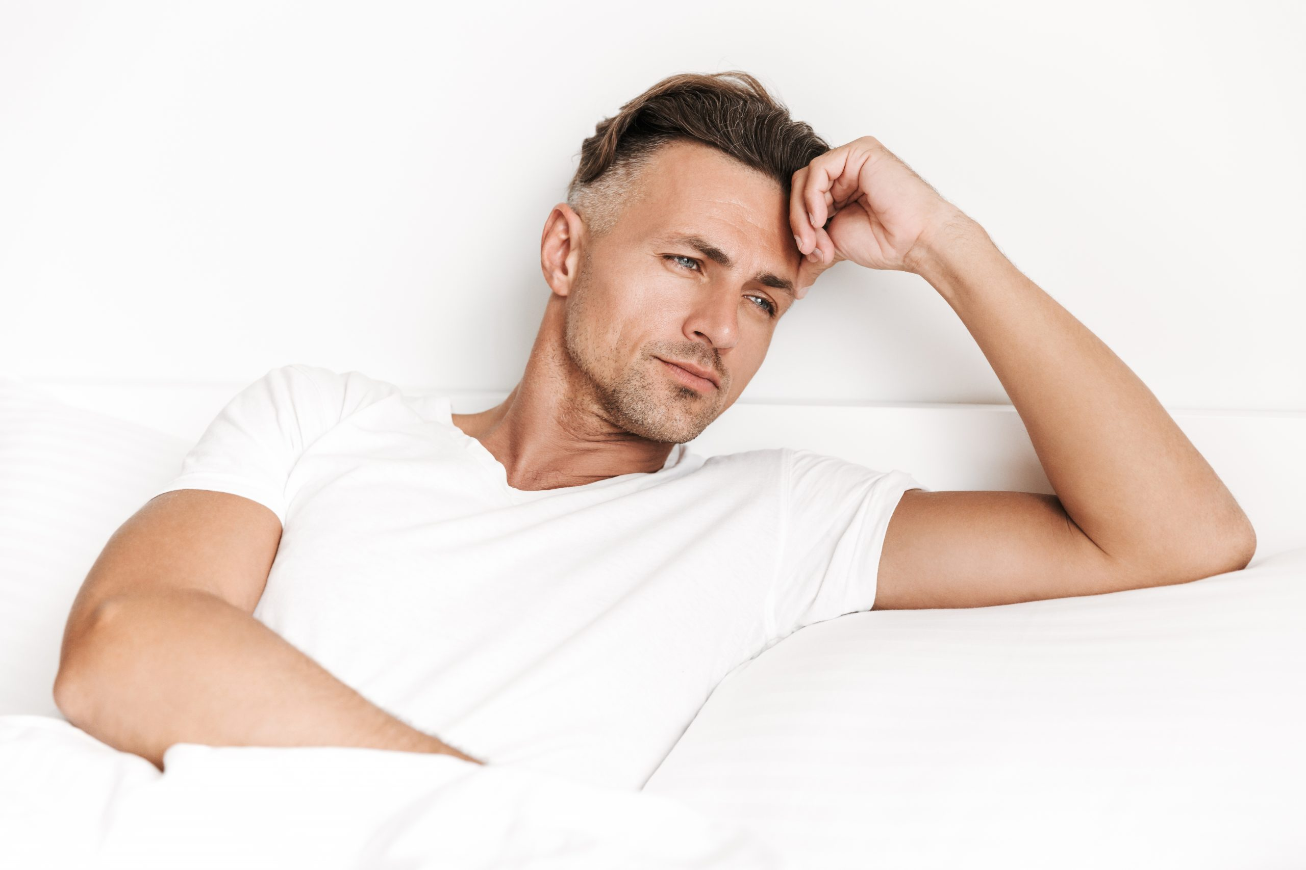 Focused man laying in bed