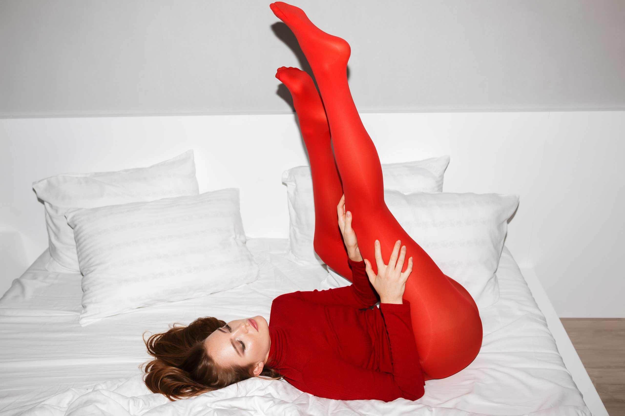 beautiful-lady-in-red-sweater-and-tights-lying-FY23H76