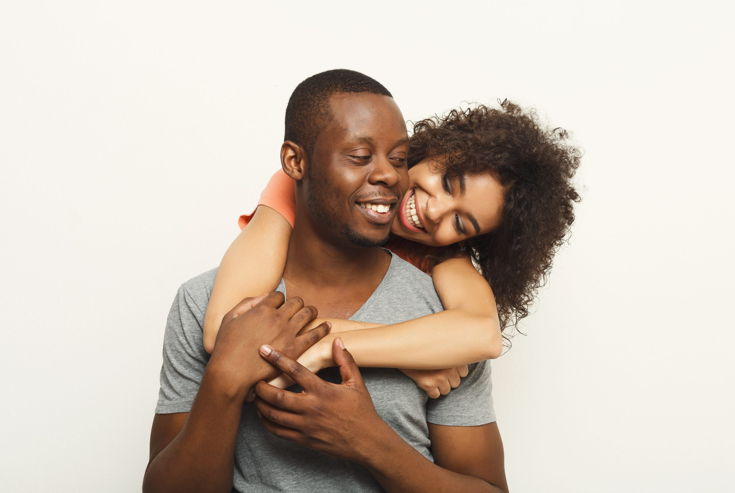 Black couple hugging and posing at white background