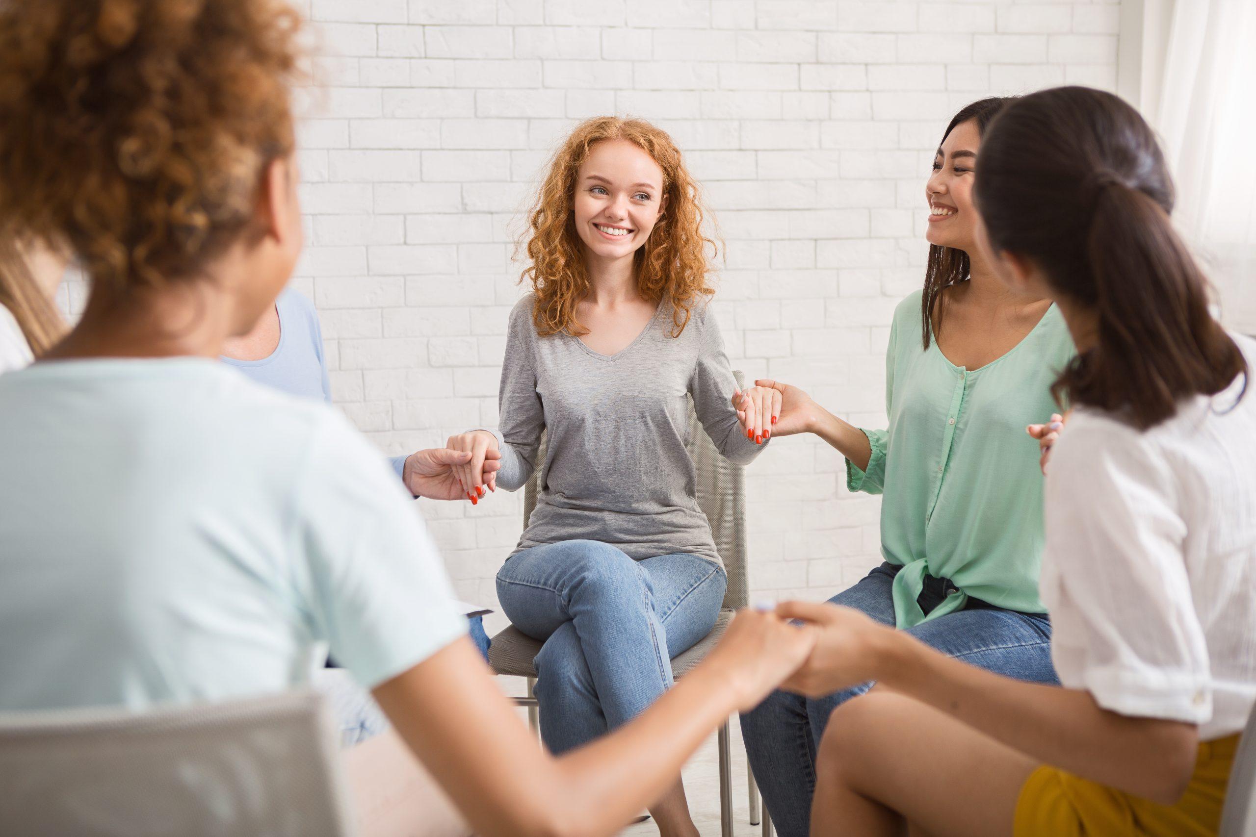 Diverse Girls Smiling Holding Hands Sitting Indoor