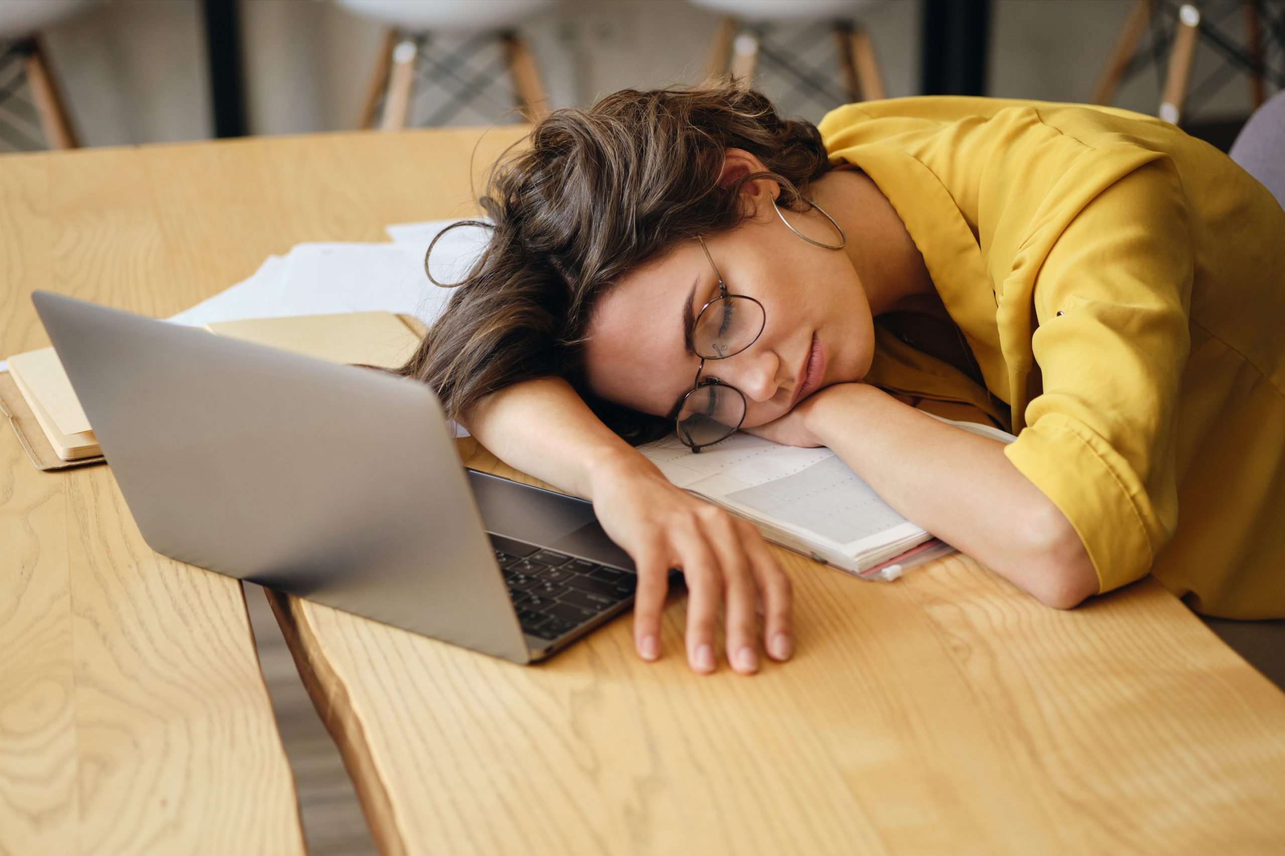 Young tired woman in eyeglasses asleep on desk with laptop and d